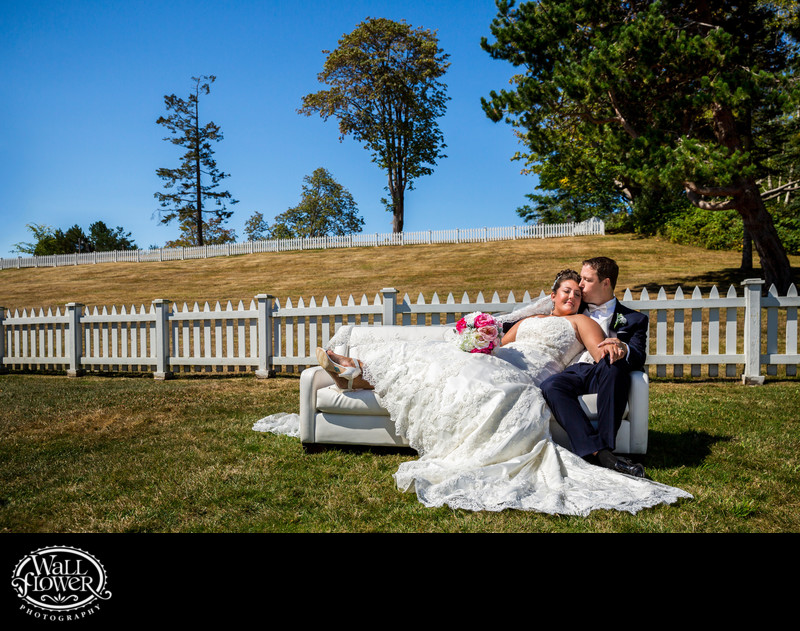 Bride reclines against groom on coach in Port Gamble
