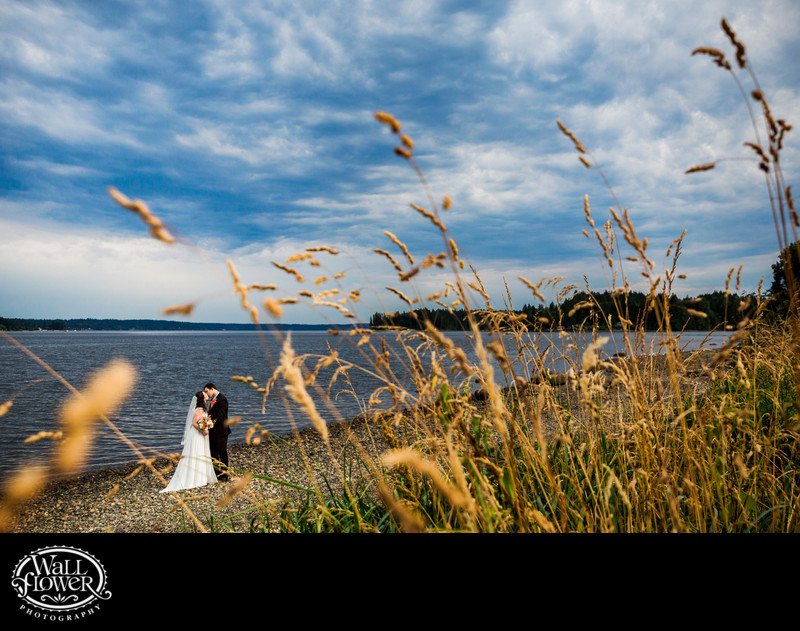 Bride and groom kiss on beach at Allyn Waterfront Park