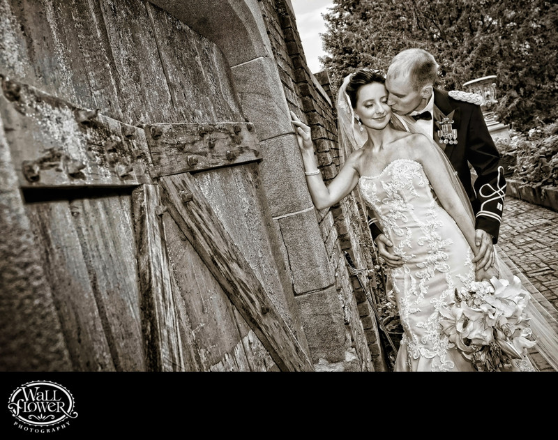 Groom kisses bride by gate to Thornewood Castle garden