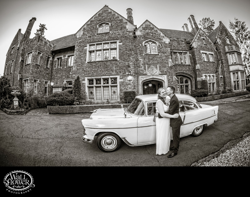 Groom kisses bride by classic car at Thornewood Castle