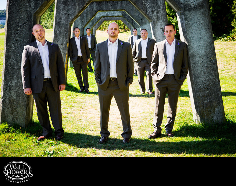 Groom, groomsmen by concrete arches at Gas Works Park