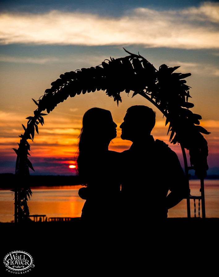 Bride and groom silhouette under wedding arch at sunset