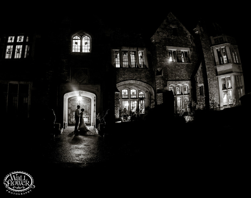 Bride and groom at night in Thornewood Castle entrance