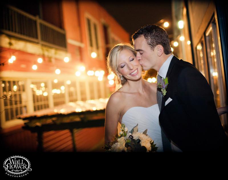 Groom kisses bride in glow of Sodo Park courtyard light