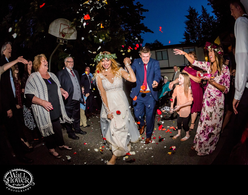 Bride and groom pelted with rose petals while departing