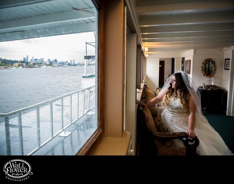 Melancholy bride by window of MV Skansonia in Seattle