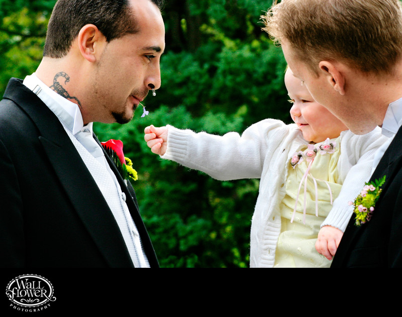 Baby reaches for flower held in tattooed groom's mouth