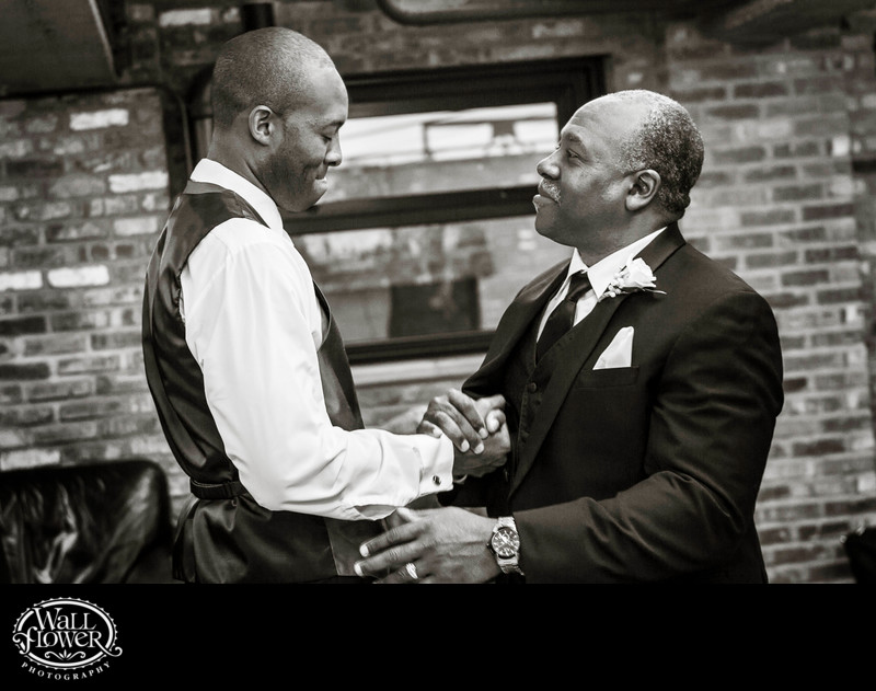 Emotional groom clasps hands with proud father