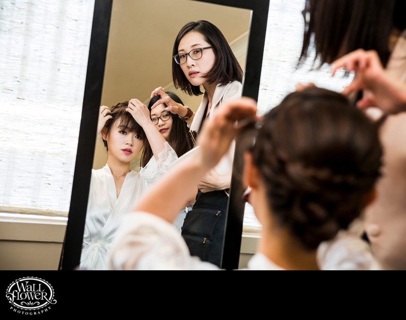 Reflection of bride adjusting hair in mirror