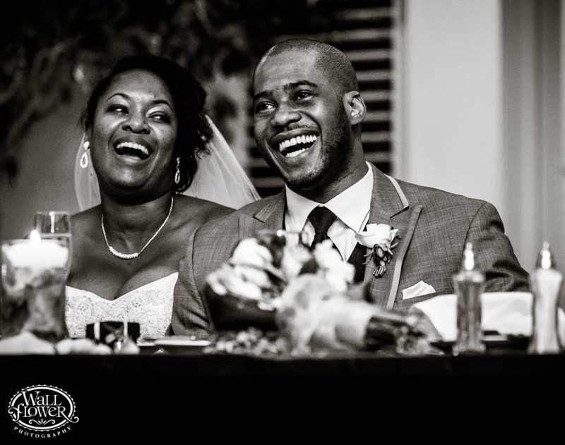 Bride, groom laugh during toasts in wedding reception