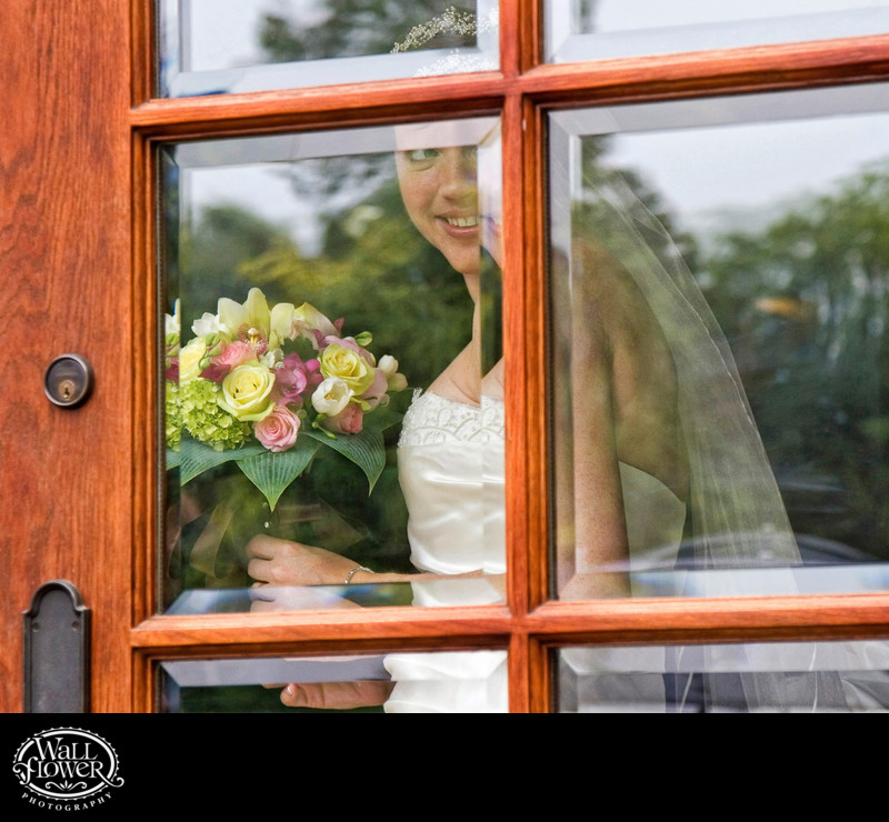 Bride looks out windows of door of Broadmoor Golf Club