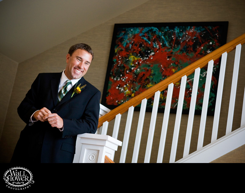 Groom smiles from staircase before wedding ceremony
