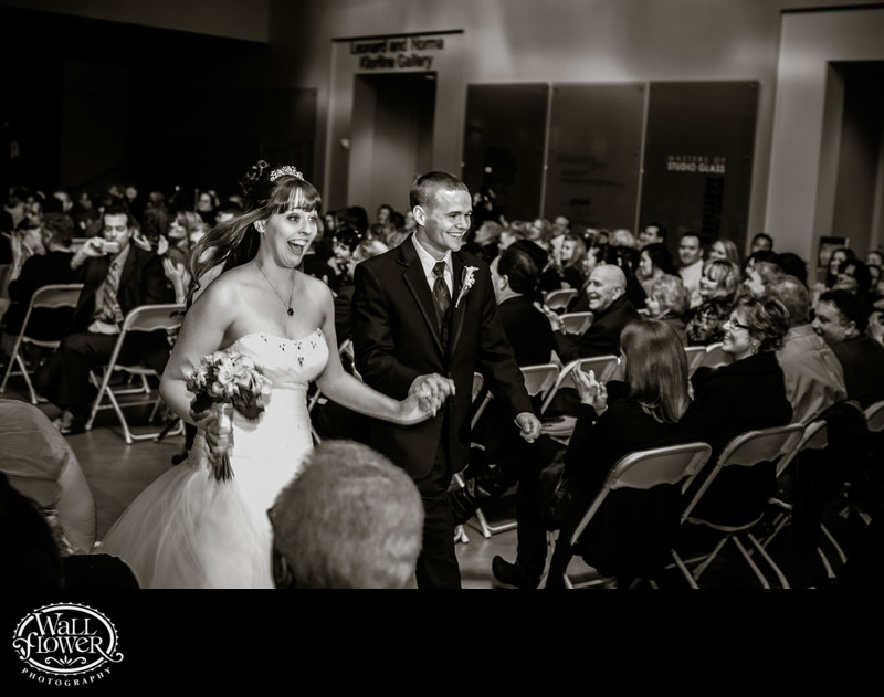 Bride and groom smile big at end of wedding ceremony