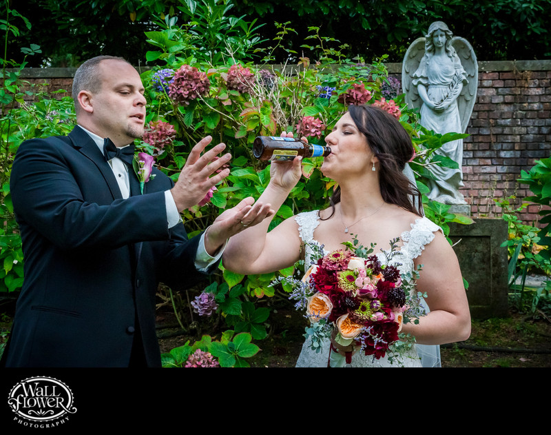 Groom attempts to rescue his beer from his thieving bride in Thornewood Castle sunken garden