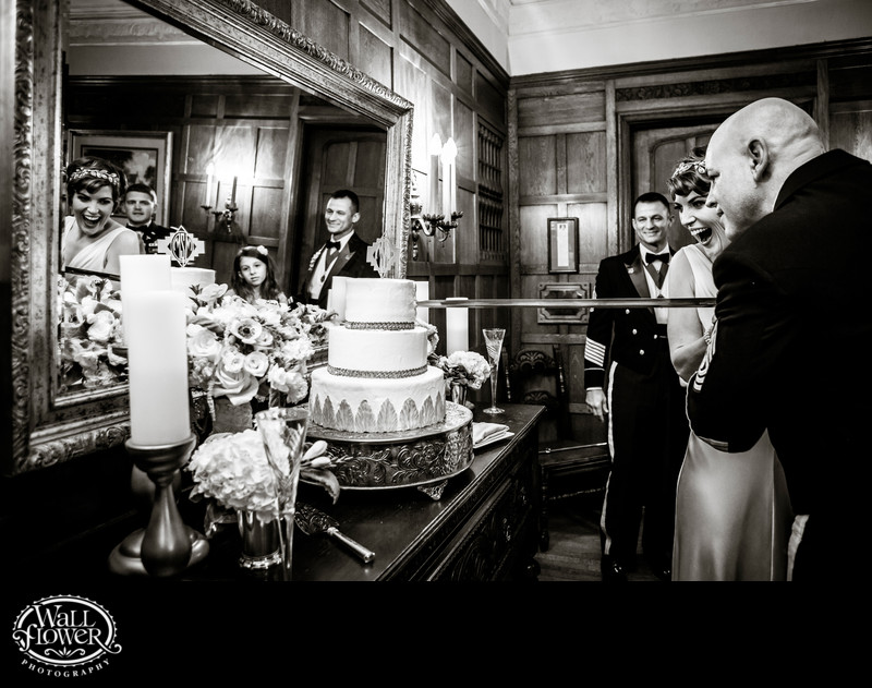 Bride and groom cut wedding cake with sword