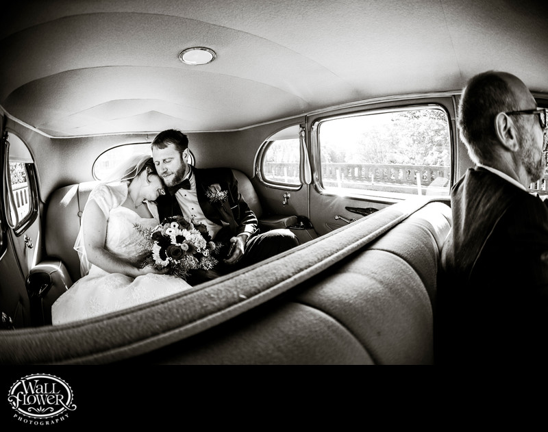 Bride snugs into groom while riding in antique Packard