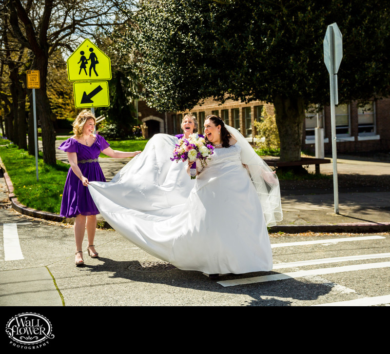 Laughing sister, mother hold bride's dress across road