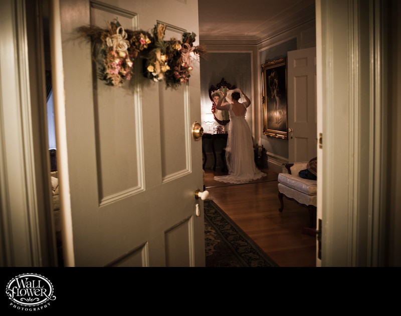 Bride adjusts veil in mirror in Thornewood Castle suite
