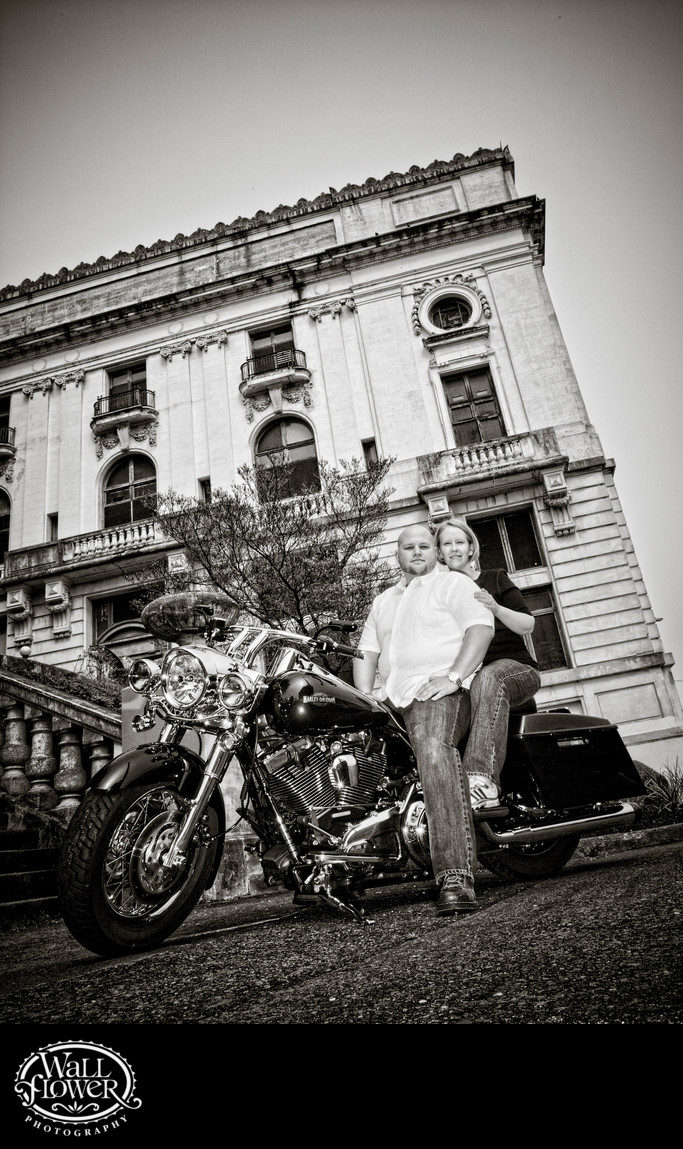 Engagement portrait of couple on Harley by Elks Temple
