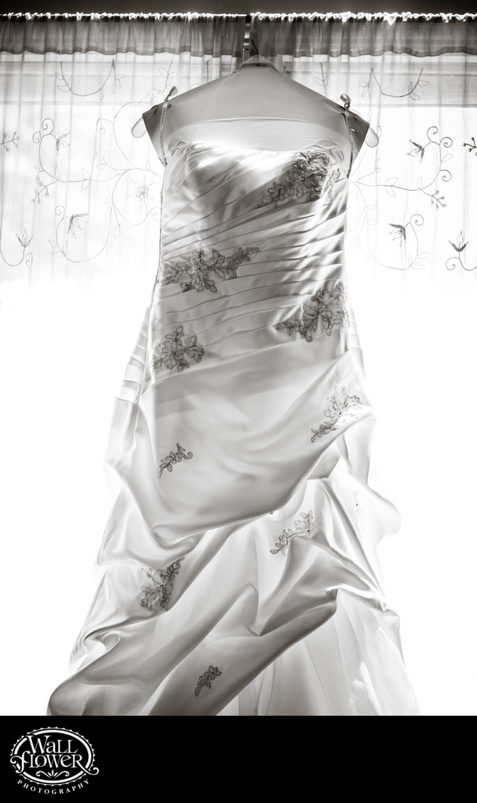 Detail of backlit wedding dress hanging in window