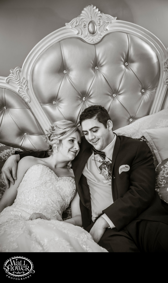 Tired bride and groom recline on Thornewood Castle bed
