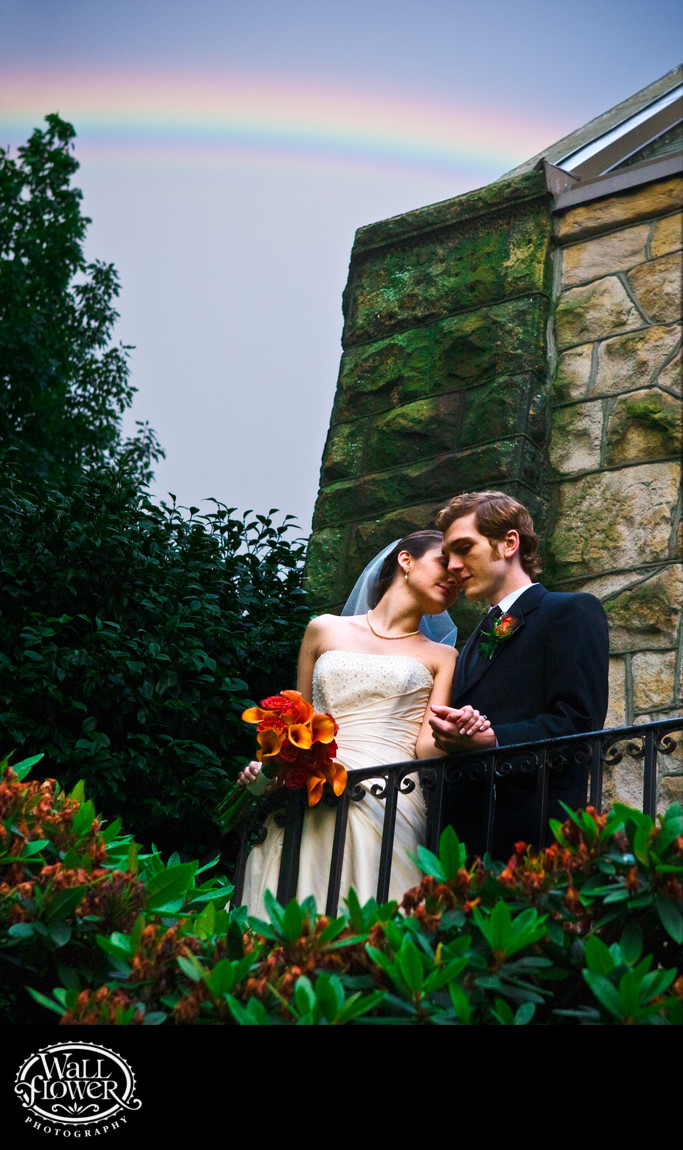 Bride and groom nuzzle under rainbow by stone church