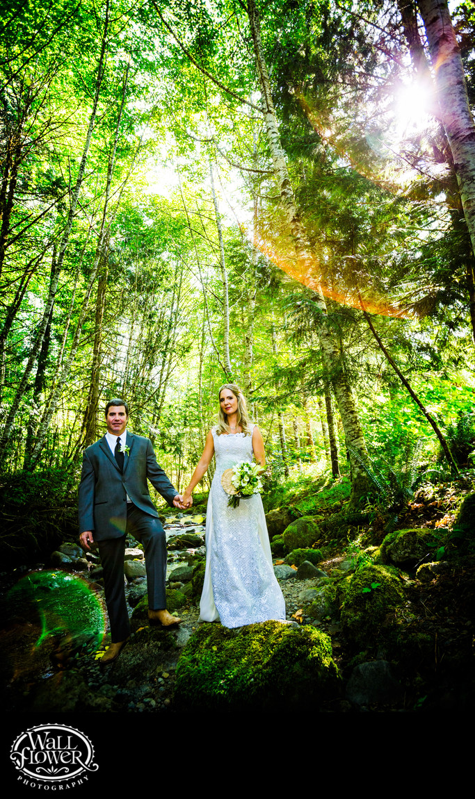 Bride and groom by forest stream at Copper Creek Inn