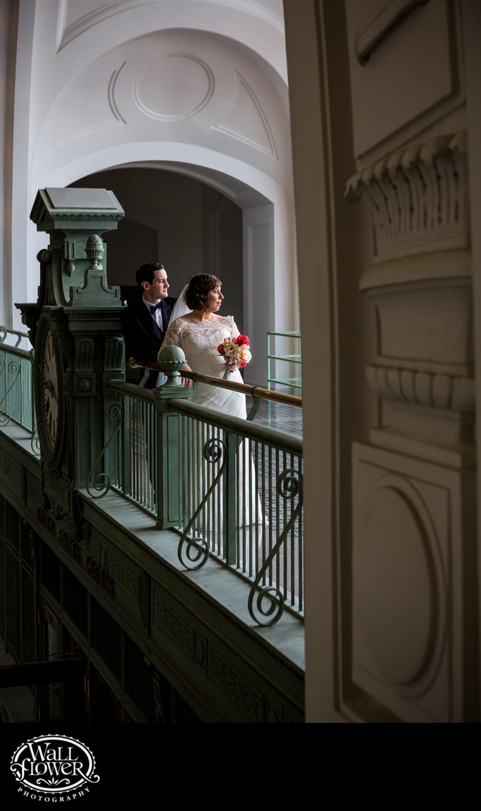 Bride and groom look out window in Tacoma Union Station
