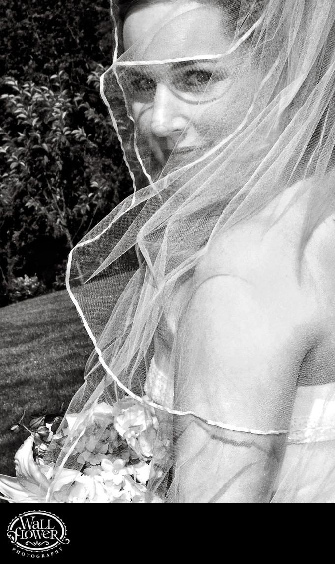 Bride smiles through veil in black and white