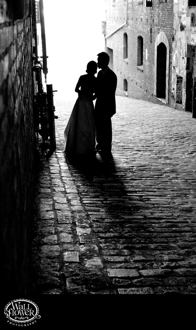 Bride and groom silhouetted on Post Alley cobblestone