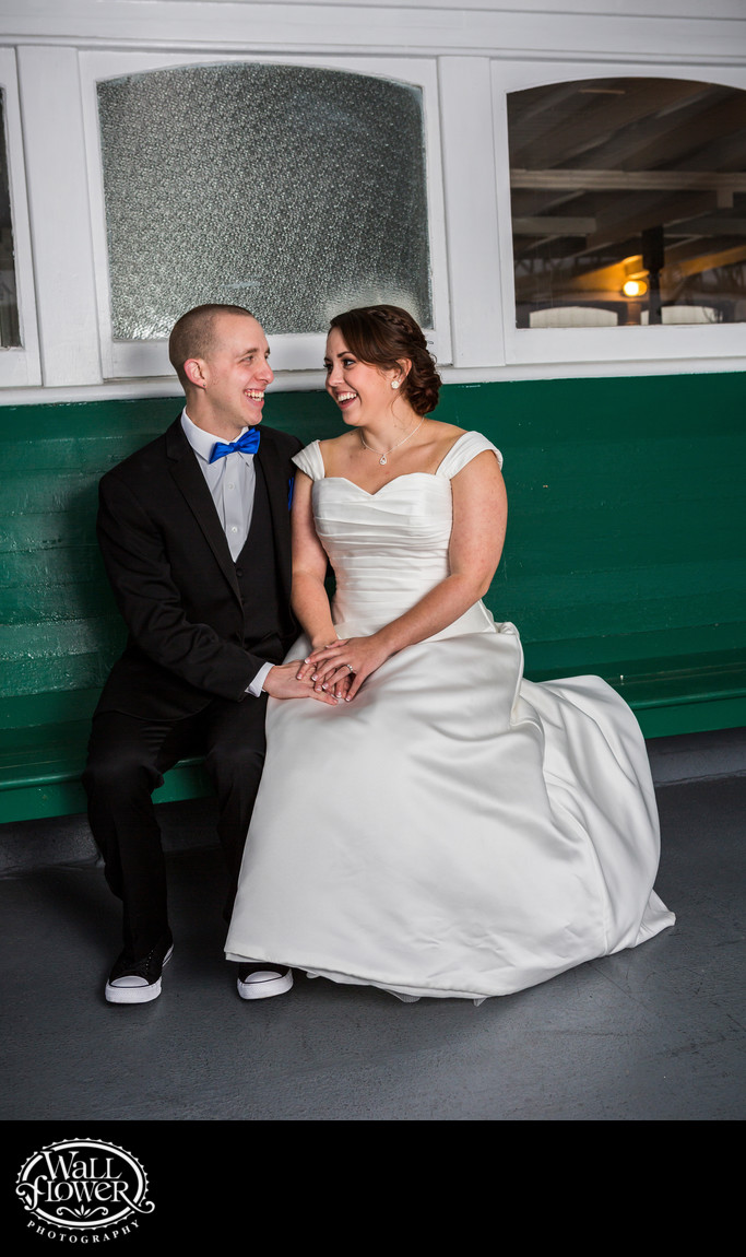 Bride and groom sit on green bench on MV Skansonia