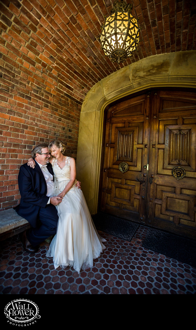 Bride and groom on bench at Thornewood Castle entrance