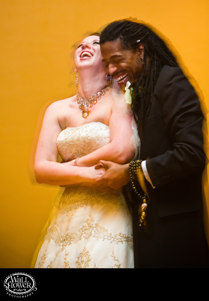 Bride and groom laugh during first dance by yellow wall