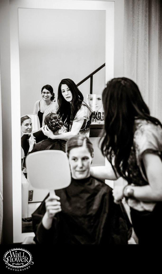 Bride is reflected twice while checking out hairdo in two mirrors at Swink in Seattle