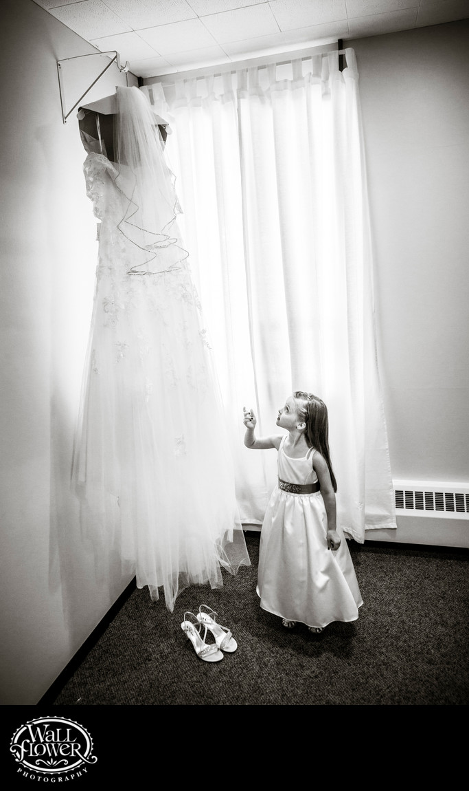 Flower girl admires bride's hanging dress