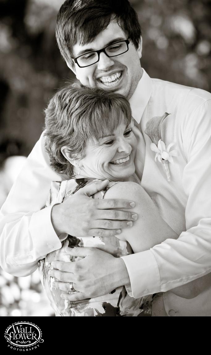 Groom hugs mother of bride during wedding reception