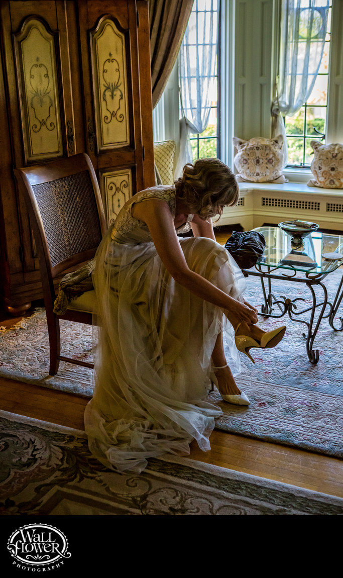 Bride puts on shoes in Thornewood Castle suite