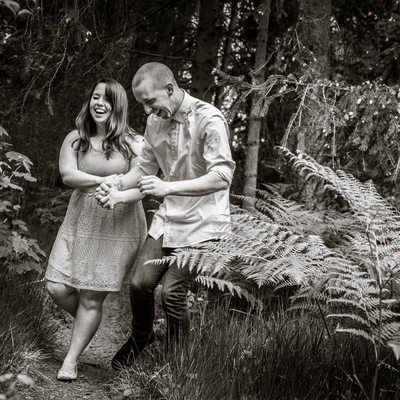 Engagement portrait of laughing couple walking