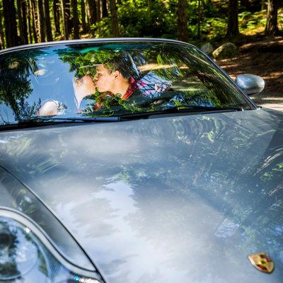 Engagement portrait kiss seen through Porsche window