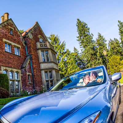 Two grooms kiss in sports car at Thornewood Castle