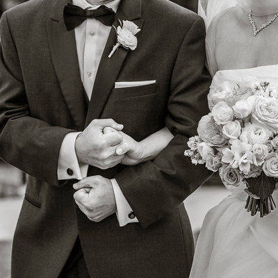 Detail of bride and father's hands in wedding ceremony