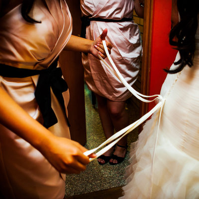 Detail of bridemaid lacing up bride's wedding dress