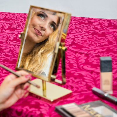 Detail of bride's reflection in makeup mirror