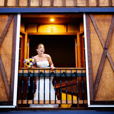 Bride prepares to toss bouquet from barn balcony
