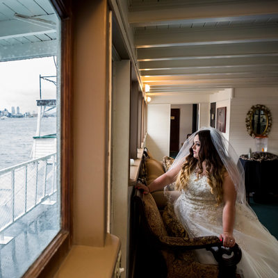 Melancholy bride by window of MV Skansonia in Seattle