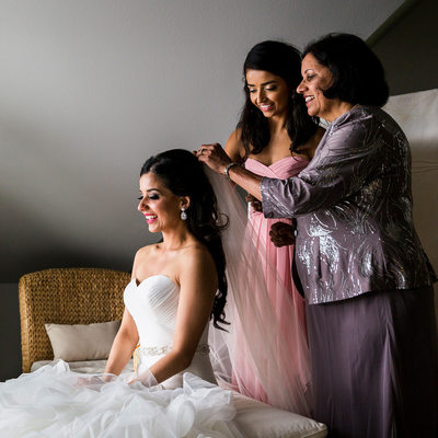 Bride's mom and sister help fasten her veil