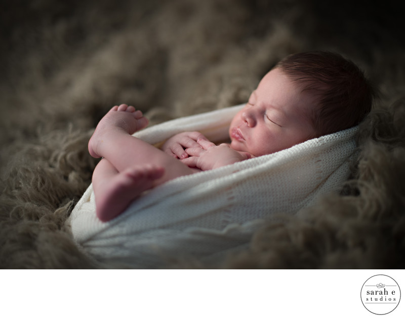Image of a Baby in Fenton, MO on a Flokati Rug Wrapped in a Scarf