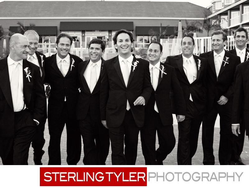 groom walking with groomsmen black white photojournalism