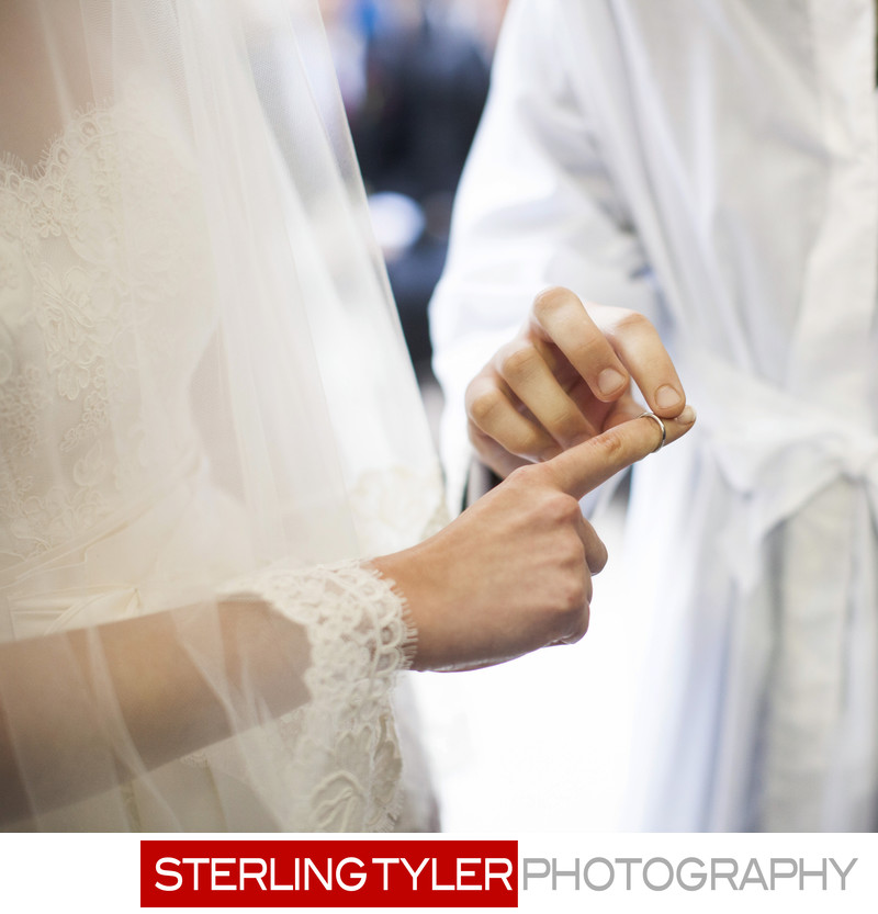 groom putting ring on bride jewish wedding photographer