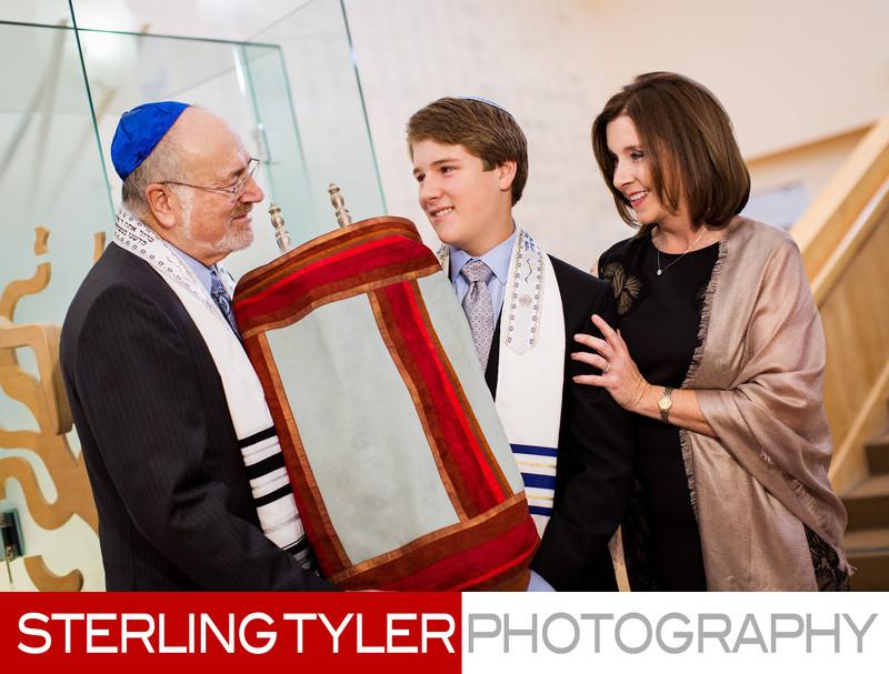 bar mitzvah boy with parents and torah at kehillat israel